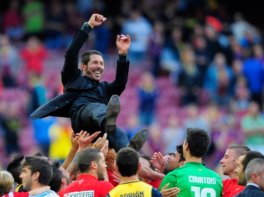 Players throw in the air Atletico's coach Diego Simeone from Argentina after a Spanish La Liga soccer match between FC Barcelona and Atletico Madrid at the Camp Nou stadium in Barcelona, Spain, Saturday, May 17, 2014. Atletico clinched its first league title in 18 years after a 1-1 draw. (AP Photo/Manu Fernandez)