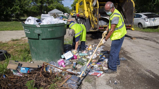 Mark Siddle, right, and Chris Johnson of Columbus's crew fighting illegal dumping clear an alley in South Linden on July 31. The city has collected 10,000 tons of illegal refuse in the past two years -- approximately the weight of the Eiffel Tower.