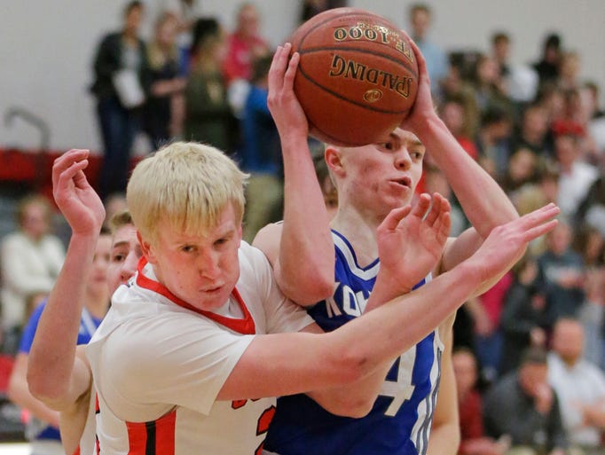 Oostburg's Adam Swart (22) works to gain the ball from