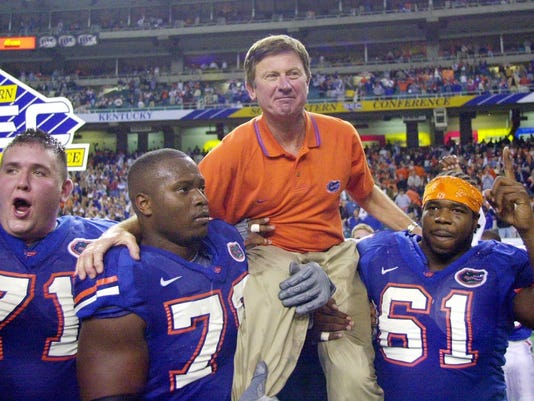 FILE - In this Dec. 2, 2000, file photo, Florida head coach Steve Spurrier is carried off the field after the Gators downed Auburn 28-6 in the SEC Championship at the Georgia Done in Atlanta. Players from left are  by Mike Pearson (71), Kenyatta Walker (78) and Gerard Warren (61).  Spurrier already has a statue outside of the football stadium and the field named after him. Next he'll serve as ambassador and consultant for the school's entire athletic department. Gators athletic director Jeremy Foley made the announcement on Friday, July 29, 2016. (AP Photo/John Bazemore, File)