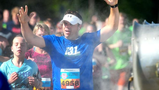 Aaron Depas, De Pere, cools off at the misting station on Libal Street during the 2014 Bellin Run, Saturday, June 14, 2014.