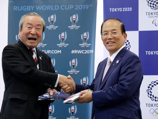 Tokyo 2020 Olympics CEO Toshiro Muto, right, and President and CEO of the 2019 Rugby World Cup Organizing Committee President and CEO Akira Shimazu exchange ties after signing a collaborative agreement in Tokyo, Wednesday, April 26, 2017. Organizers of the 2020 Olympics signed a collaborative agreement with the organizers of the 2019 Rugby World Cup, aiming to maximize the benefits and impact of the global events. The Rugby World Cup will be staged in Japan as Tokyo is finalizing preparations to host the Summer Games for the first time since 1964. (AP Photo/Eugene Hoshiko)