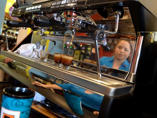 Co-owner Erica Brooks is reflected in the espresso machine as she fills up two shots of the drink Monday, Jan. 25, at the new Biggby Coffee location in Fort Gratiot.