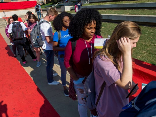 "University of Tennessee students line up in between classes to pledge to speak up against sexual assault and receive a ""does not mean yes"" t-shirt during a Red Zone event held outside of the Alumni Memorial Building on UT's campus on Monday, Sept. 18, 2017."