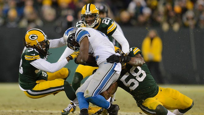 Green Bay Packers defenders Tramon Williams (37), Sam Barrington (58) and Ha Ha Clinton-Dix (21) tackle Detroit Lions receiver Jeremy Ross (12) in the fourth quarter during Sunday's game at Lambeau Field.