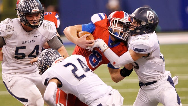 Central Catholic Jackson Anthrop and Adam Lovell combine to stop Pierce Jackson of Linton-Stockton square in the Class A state finals Friday, November 27, 2015, at Lucas Oil Stadium in Indianapolis. Central Catholic defeated Linton-Stockton 34-7.