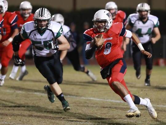 Tulare Western's Andre Aguilar rushes past Tehachapi's Jackson Caudle in Thursday's Central Section Division III quarterfinal high school football game at Bob Mathias Stadium.