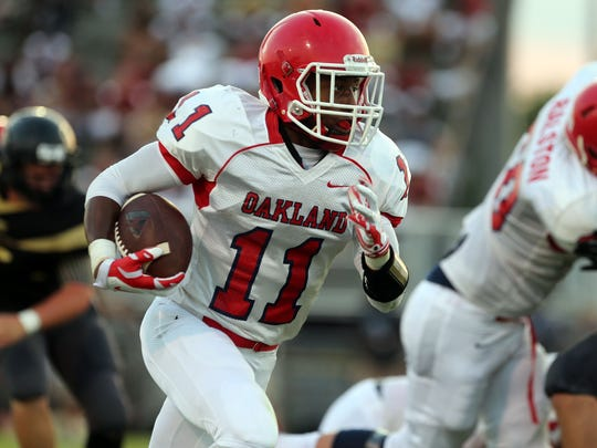Oakland's Josh Cunningham rushes against Mt. Juliet during the football jamboree Friday, August 15, 2014 at Smyrna High School.