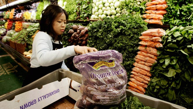 Ming Yee stocks shelves in the organic produce section at the Whole Foods Market in Willowbrook, Ill., on Jan. 5, 2006. Whole Foods Market along with other organic food distributors are trying to bring down the cost of organic foods to attract the family on a budget.