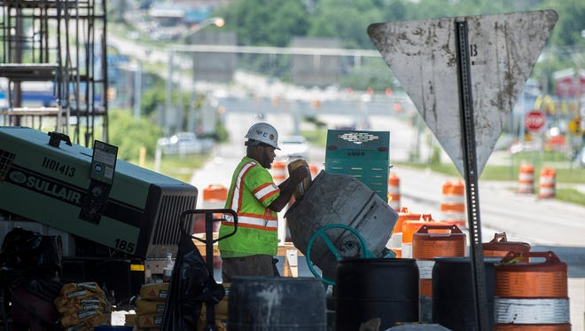 Construction workers with Blakley's Corp. work on concrete portions of an Interstate 70 overpass near the Indiana-Ohio border on Monday, July 9, 2018.