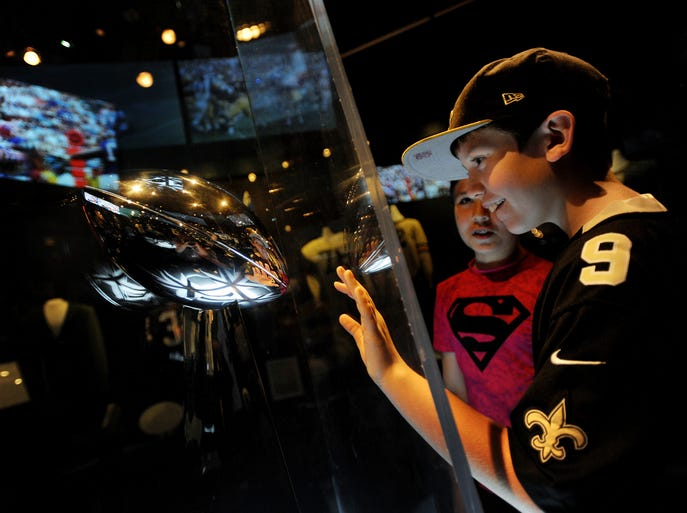 "Ryan Yantus, left, 11, and Joey Fitzgibbons, 11, both from Macomb, get an up-close moment with the Vince Lombardi trophy displayed in the Champions Theater at ""Gridiron Glory: The Best of the Pro Football Hall of Fame"" exhibit at the Henry Ford Museum in Dearborn, Michigan on October 5, 2014. The traveling exhibit, from the Pro Football Hall of Fame in Canton, Ohio, offers a panoramic view of professional football from its humble beginnings in the early 20th century to the phenomenon it is today, said Melissa Foster, spokeswoman for The Henry Ford."