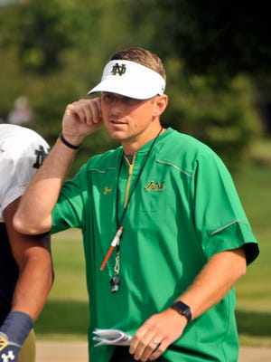 In this Saturday, Aug. 15, 2015, photo, Notre Dame offensive coordinator Mike Sanford walks onto the practice field during an  NCAA college football practice in South Bend, Ind.