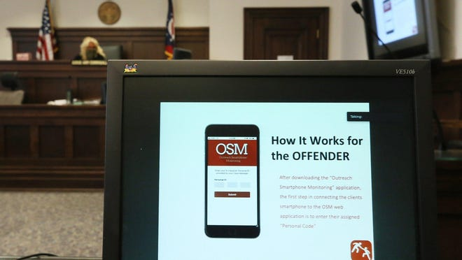 Summit County Common Pleas Judge Amy Corrigall Jones watches a presentation on Outreach Smartphone Monitoring, a new probation app for 1,000 people on probation, in her courtroom May 19.