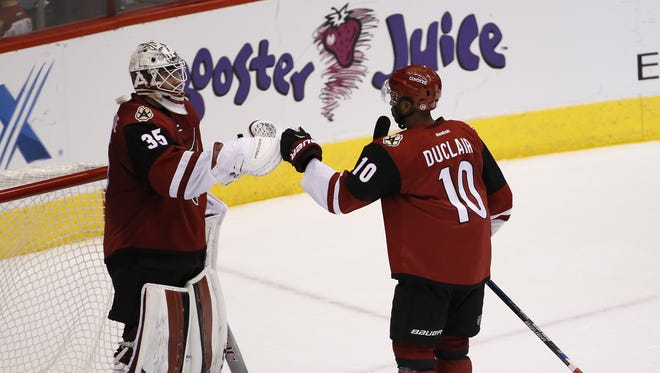 Arizona Coyotes goalie Louis Domingue and forward Anthony Duclair celebrate their 3-2 victory against the Toronto Maple Leafs at Gila River Arena in Glendale December 22, 2015.