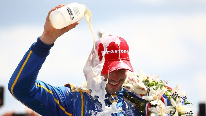 Alexander Rossi celebrates his with with the traditional bottle of milk.