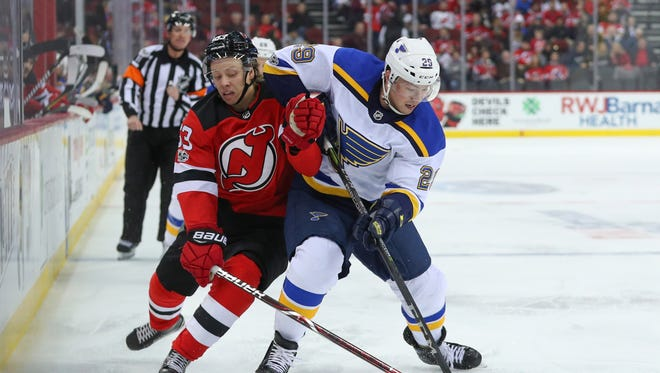 St. Louis Blues defenseman Vince Dunn (29) and New Jersey Devils left wing Jesper Bratt (63) battle for the puck during the second period at Prudential Center.