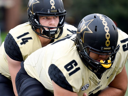 Vanderbilt quarterback Kyle Shurmur (14) runs drills with guard Bruno Reagan (61) before a game against Western Kentucky last season.