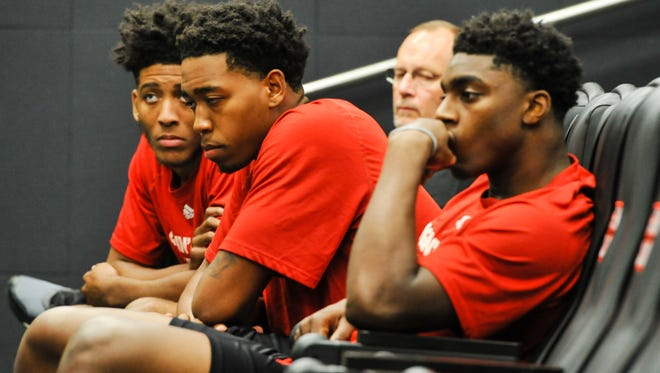 UL players Roydell Brown, left, Bryce Washington, center and Frank Bartley IV, right wait for their turn to pay tribute to fallen teammate Herman Williams during Tuesday's press conference.