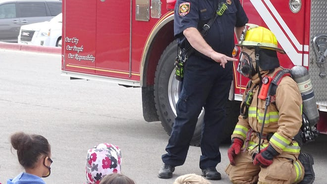 The Ottawa Fire Department visits with Sharla Testorff's Sunflower Elementary kindergarten class. The firefighters showed how they put on the fire equipment and explained why each part in necessary. October is Fire Safety Month.