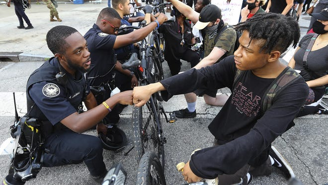 Atlanta Police Officer J. Coleman, left, and protester Elijah Raffington, of Sandy Springs, fist bump while an Atlanta Police bicycle unit blocking Marietta Street at Centennial Olympic Park Drive kneels down with protesters in a symbolic gesture of solidarity outside the CNN Center at Olympic Park, Wednesday, June 3, 2020, in Atlanta, during a protest sparked by the May 25 death of George Floyd in Minneapolis police custody.