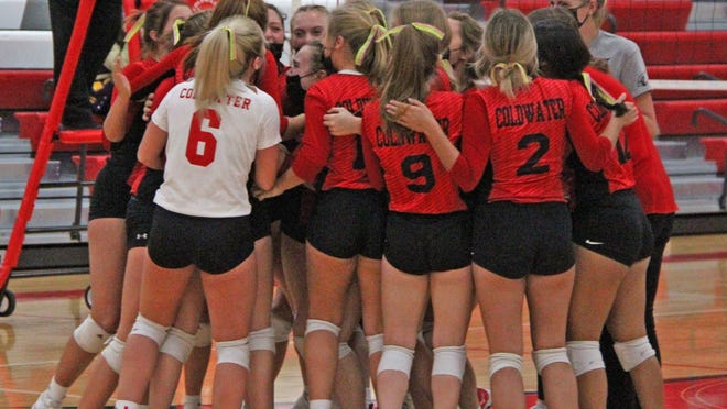 The Coldwater Lady Cardinals celebrate their five set slugfest win over Holt Monday night in the first round of Division One District play.