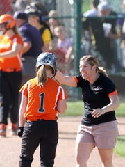 North Union softball coach Dawn Draper greets Cheyenne Wiley at third base after her big hit in a 12-2 district championship win in 2014.