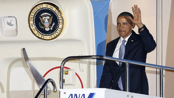 U.S. President Barack Obama waves from the doorway of Air Force One upon his arrival at Haneda International Airport in Tokyo, Wednesday, April 23, 2014. Obama is in Japan for a three-day state visit. (AP Photo/Shizuo Kambayashi)