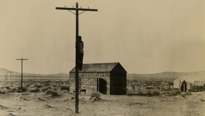 """The body of William """"Red"""" Wood hangs from a telegraph pole in Hazen in 1905."""