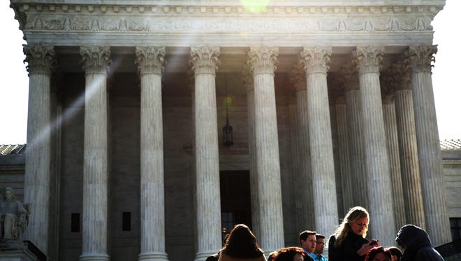 People wait in-line to enter the U.S. Supreme Court to hear oral arguments April 22, 2014