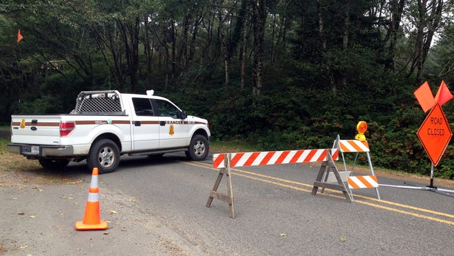 A road block closes access to Bastendorf Beach outside Coos Bay, Ore., on Tuesday, Aug. 19, 2014, where authorities say a drive-by gunman shot five vehicles, killing a Michigan man as he slept, then shot and killed himself.
