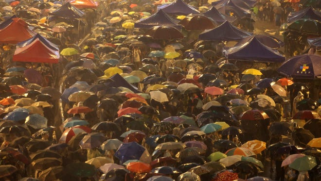 Pro-democracy protesters hold umbrellas under heavy rain in a main street near the government headquarters in Hong Kong.