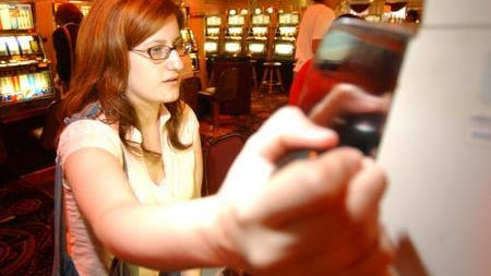 Amy Witherby, from Taylor Creek, Kentucky, pulls the handle in 2005 for the slot machine while gambling at Grand Victoria Casino in Rising Sun, Indiana.
