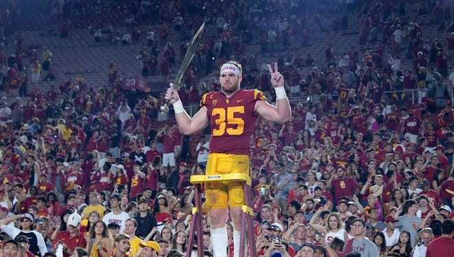 USC Trojans linebacker Cameron Smith (35) conducts the Spirit of Troy marching band after a NCAA football game against the Stanford Cardinal at Los Angeles Memorial Coliseum. USC defeated Stanford 42-24.