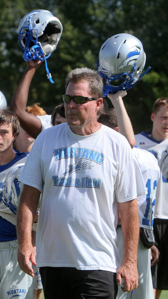 Coach Robert Hannah leads the River Oaks Mustangs onto the practice field on Wednesday, Aug. 20, 2014.