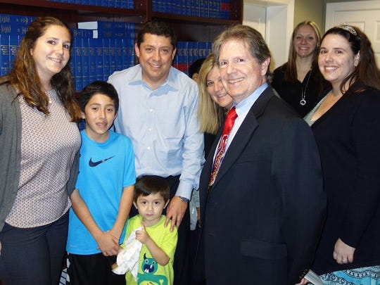 The Mendiolaza family, center, dad Jose and brothers Nicholas and Andre, are seen with attorney Bill Morros and staff members.