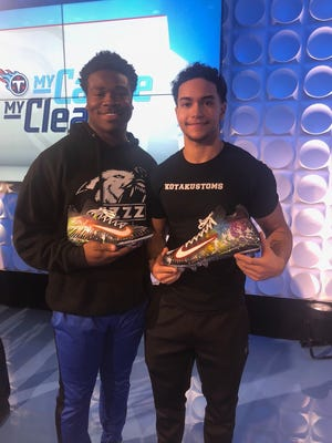 """Dakota Wiley (right), the 19-year-old brother-in-law of Titans running back David Fluellen, presents linebacker Jayon Brown with the cleats he designed for him for the NFL's """"My Cleats, My Cause"""" campaign. November 2018."""