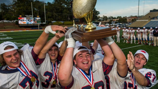 Lamar School seniors hoist the trophy following their 28-7 win over Oak Forest (La.) in the MAIS AAAA-Division II championship at Mississippi College in Clinton on Friday.