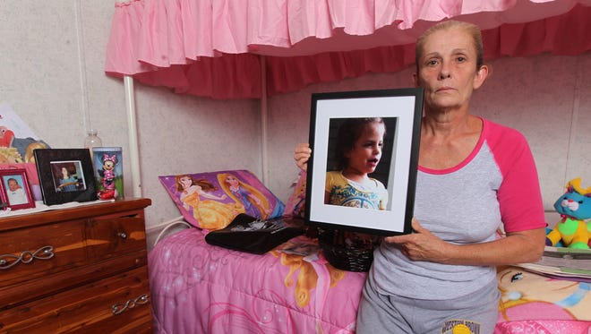Rae Ann Mills of Batavia Township holds a photo of her granddaughter, Kylie Mills, 6, who drowned in a pond at Camp Allyn.