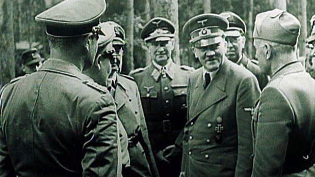 Adolf Hitler meets with some of his military commanders against the forested background of Wolf's Lair, in what is now Poland.