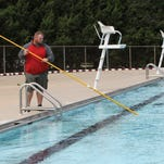 Dustin Gainer vacuums Meador Pool on Monday to get it ready to open for the season last year. Meador will be closed for at least a week, but other pools are open for the season.