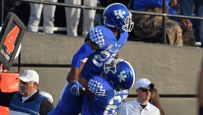 Kentucky Wildcats running back Sihiem King (22) celebrates with center Jervontius Stallings (65) after scoring a touchdown against the Vanderbilt Commodores during the first half at Vanderbilt Stadium in Nashville, Tennessee, on Saturday, Nov. 11, 2017.