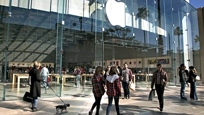 In this Saturday, Jan. 3, 2015 photo, shoppers walk by the Apple Store along the the Third Street Promenade in Santa Monica, Calif.