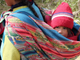 An infant stays bundled up while being carried.