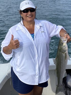 UMass Memorial physician's assistant Donna Reich takes a break from COVID-19 duties, releasing a Billingsgate Shoals striper.
