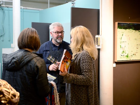 Artist Matt Tommey talks with Ann Smith and Kim Turpin, both of Leap Frog Tours, March 8 at his studio in the River Arts District.