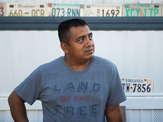 "Alberto Librado, in a ""Land of the free"" shirt, stands outside his home in White Pine, Tenn. July 3, 2018. He was detained by U.S. Immigration and Customs Enforcement agents when they raided the Southeastern Provision meat-packing plant where he worked outside Bean Station in April."