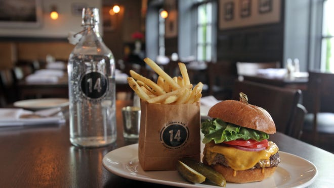 Saturday Night Burger with cheese, lettuce tomato and paper bag fries is served at 14 and Hudson kitchen and bar in Piermont.