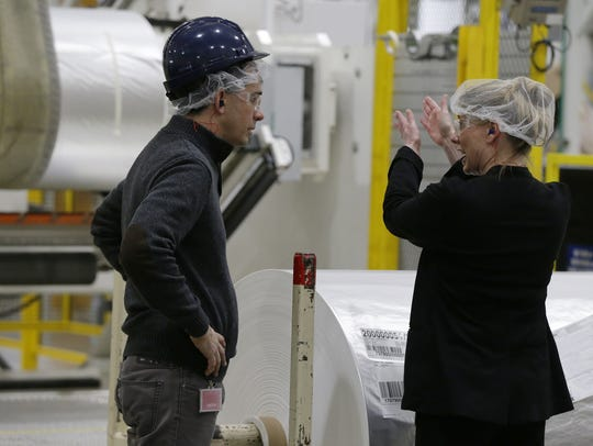Gov. Scott Walker chats with an employee at Bemis Corp.'s