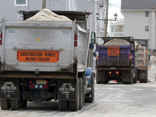 Trucks filled with sand are shown along Ocean Avenue