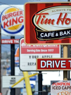File photo taken in 2014 shows signs for a Tim Hortons restaurant, foreground, and a Burger King restaurant in Erie Pa.